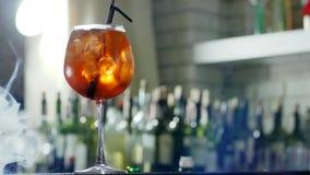 Яркое питье спирта с кубами льда и пластичной соломой в крупном плане рюмки в легкий помох на несосредоточенной предпосылке видеоматериал