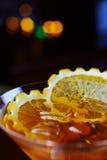 Яркое стекло очень вкусного коктеиля или лимонада Мартини алкоголички с льдом и кусок апельсина на таблице в баре или ресторане Стоковые Фотографии RF
