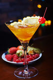 Яркое стекло очень вкусного коктеиля или лимонада Мартини алкоголички с льдом и кусок апельсина на таблице в баре или ресторане Стоковая Фотография