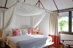 Ярко освещенная комната кровати современного деревянного дома в тропической стране Стоковая Фотография