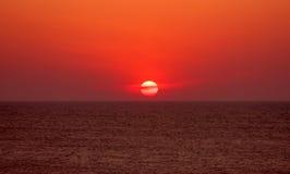 Ярко покрашенное солнце во время захода солнца через облака в море Стоковая Фотография RF
