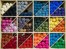 Ярко покрашенные пасма шерстей организованных цветом на триангулярных полках Стоковая Фотография RF