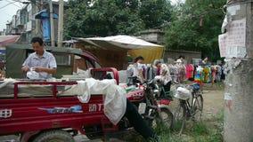 Ярмарки городка Китая выходят на рынок, который 3-катят мотоцикл, продавая одежды сток-видео