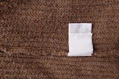 Ярлыки одежды на деревянной предпосылке Стоковое Фото