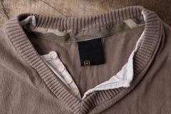 Ярлыки одежды на деревянной предпосылке Стоковое фото RF