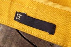 Ярлыки одежды на деревянной предпосылке Стоковая Фотография RF