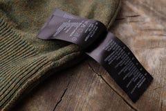 Ярлыки одежды на деревянной предпосылке Стоковая Фотография