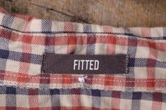 Ярлыки одежды на деревянной предпосылке Стоковые Изображения