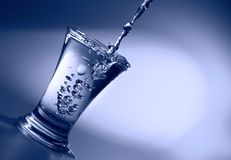 ясная жидкость льет рюмку Стоковое Изображение