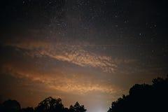 Ясное ночное небо с холмом и деревьями на переднем плане Стоковое Изображение RF