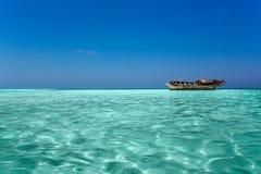 Ясный океан Мальдивы мочит под голубым небом с покинутой шлюпкой Стоковые Фотографии RF