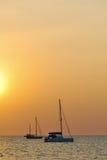 Яхта на пляже во время захода солнца стоковые изображения