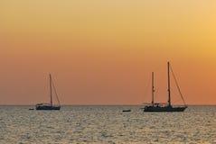 Яхта на пляже во время захода солнца стоковые фото