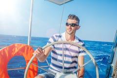 Яхта плавания молодого человека Праздники, люди, перемещение стоковая фотография