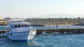 Яхта с флагом стоит около пристани акции видеоматериалы