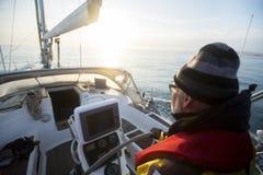 Яхта управления рулем человека на кормиле во время захода солнца Стоковые Фотографии RF