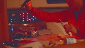 Яхтсмен в красном пальто сидит на таблице болтовни для формировать курс яхты акции видеоматериалы