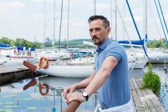 Яхтсмен стоя близко барьера пристани с шлюпками Бородатый человек смотря к далеко перед путешествием близко яхты Стоковая Фотография RF