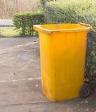 Ящики хлама желтых мусорных корзин trashcan в саде Стоковые Фотографии RF