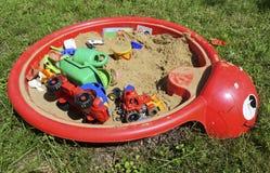Ящик с песком детей с игрушками на траве Стоковое фото RF