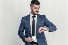 Я должен находиться там во времени Уверенный бизнесмен смотря на его наручных часах и держит его coffe изолированный на белой пре стоковая фотография