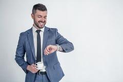 Я должен находиться там во времени Усмехаясь бизнесмен смотря на его наручных часах и держит его coffe изолированный на белой пре стоковые фотографии rf