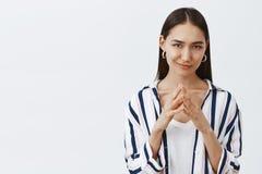 Я имею большой злий план Симпатичная уверенно и каверзная женщина в striped блузке, держа пальцы совместно и ухмыляться стоковые фотографии rf