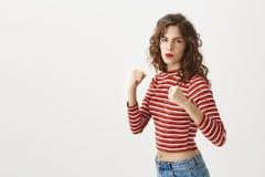Я постучаю вами для того чтобы опустить при мой левый кулак серьезный и уверенно стильное в защиту рук повышения женщины, стоя вн стоковая фотография