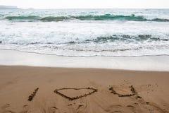 Я тебя люблю нарисованный в песке греческого пляжа с водой бирюзы стоковые изображения rf