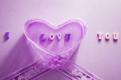 Я тебя люблю помечающ буквами с лентой на фиолетовой предпосылке Принципиальная схема дня ` s Валентайн Стоковое Изображение RF