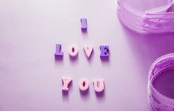 Я тебя люблю помечающ буквами с лентой на фиолетовой предпосылке Принципиальная схема дня ` s Валентайн Стоковая Фотография RF