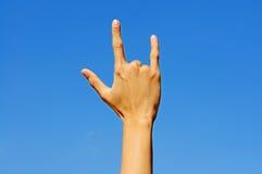 Я тебя люблю в языке жестов руки на предпосылке голубого неба. Стоковые Изображения