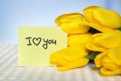 Я тебя люблю, карточка с словами и желтые тюльпаны цветут Стоковое фото RF