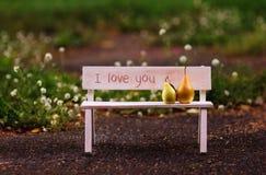 я тебя люблю Пары влюбленности сидя на стенде Стоковые Изображения