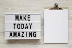 '做今天令人惊讶的'词在一个灯箱,有空白的纸片的剪贴板在白色木背景的 从上面,overhea 图库摄影