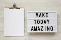 '做今天令人惊讶的'词在lightbox,有空白的纸片的剪贴板在白色木背景的 r 免版税库存图片