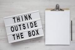 '在一个灯箱的箱子的词,有空白的纸片的剪贴板之外认为在白色木背景的,顶视图 ??l 库存图片