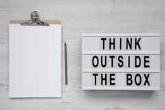 '在一个现代委员会的箱子的词,有空白的纸片的剪贴板之外认为在白色木背景的,顶视图 fla 库存照片