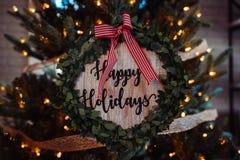 '在与红色镶边丝带的木装饰写的节日快乐的 免版税库存图片
