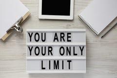 '您是您在一个现代板,有空白的纸片的剪贴板的唯一的极限'词,片剂,在白色木的笔记薄 图库摄影