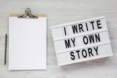 '我在一个现代板,有空白的纸片的剪贴板写我自己的故事'词白色木表面上的,顶视图 ? 库存图片