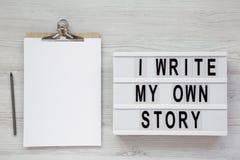 '我在lightbox,有空白的纸片的剪贴板写我自己的故事'词在白色木背景的,顶视图 从土佬 库存图片