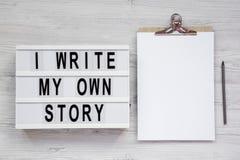 '我在lightbox,有空白的纸片的剪贴板写我自己的故事'词白色木表面上的,顶视图 r 库存图片
