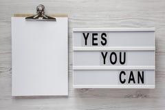 '是您能'在一个现代板,有空白的纸片的剪贴板的词在白色木表面,顶视图的 在头顶上,从 免版税库存照片