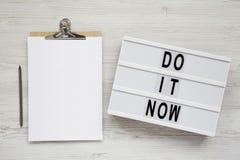 '现在做它'在一个现代板,有空白的纸片的剪贴板的词白色木表面上的,顶视图 r 免版税图库摄影