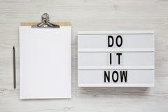 '现在做它'在lightbox,有空白的纸片的剪贴板的词在白色木背景的,顶视图 平的位置,顶上, 图库摄影
