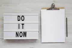 '现在做它'在lightbox,有空白的纸片的剪贴板的词白色木表面上的,顶视图 平的位置,天花板,fr 库存照片