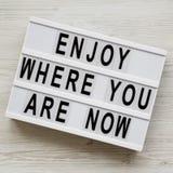 'Aprecie onde você é agora 'palavras na placa moderna sobre a superfície de madeira branca, vista superior Configuração lisa, de  imagem de stock royalty free