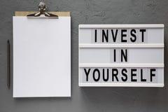 'Invierta en sí mismo 'las palabras en un tablero moderno, tablero con la hoja de papel en blanco sobre el fondo concreto, visión foto de archivo