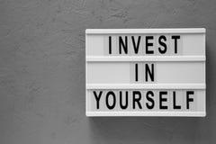 'Invierta en sí mismo 'las palabras en un tablero moderno sobre el fondo concreto, visión superior Endecha de arriba, plana, desd fotografía de archivo